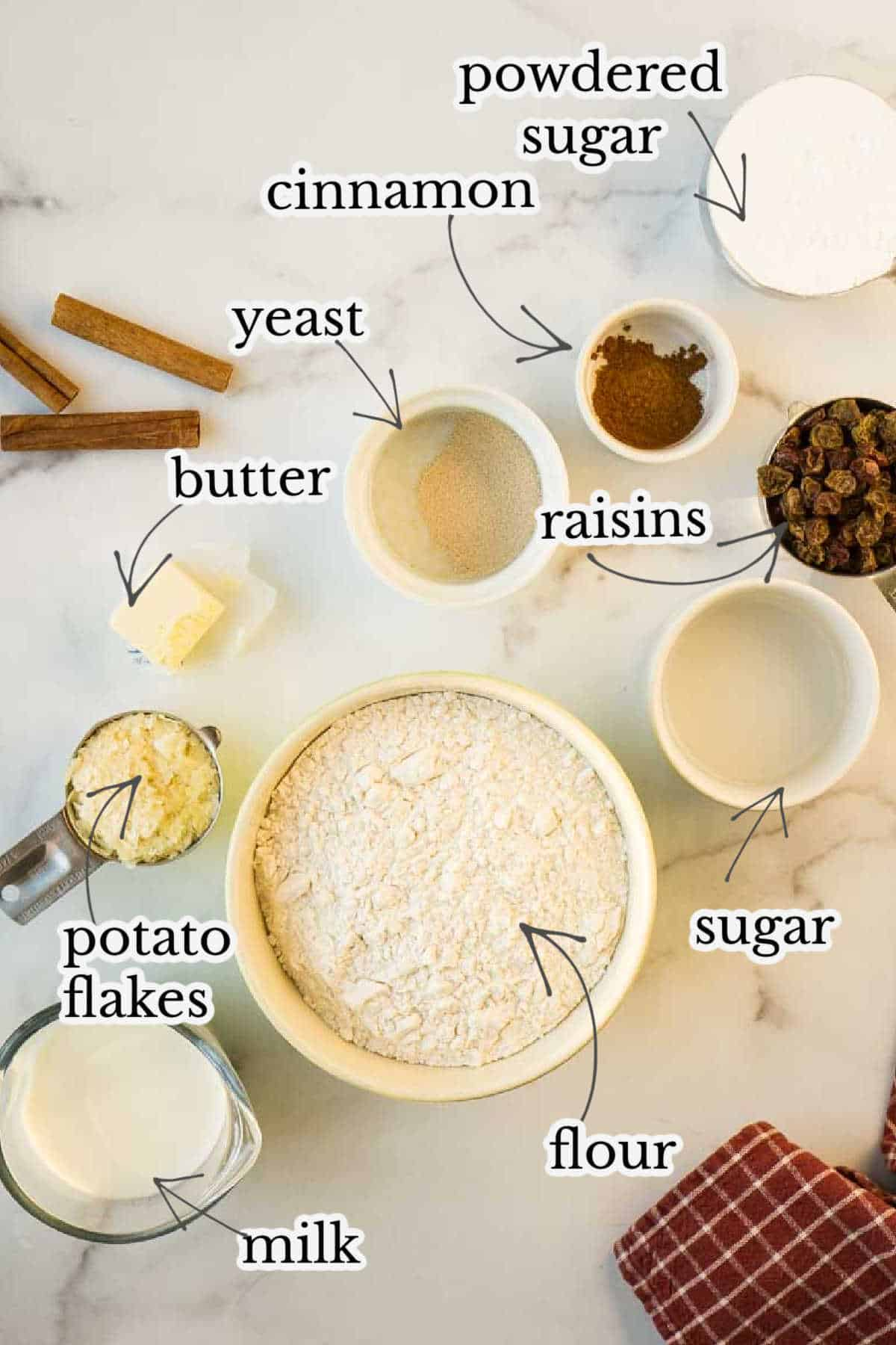 flour, sugar, cinnamon, yeast, raisins, butter, and other ingredients in small bowls