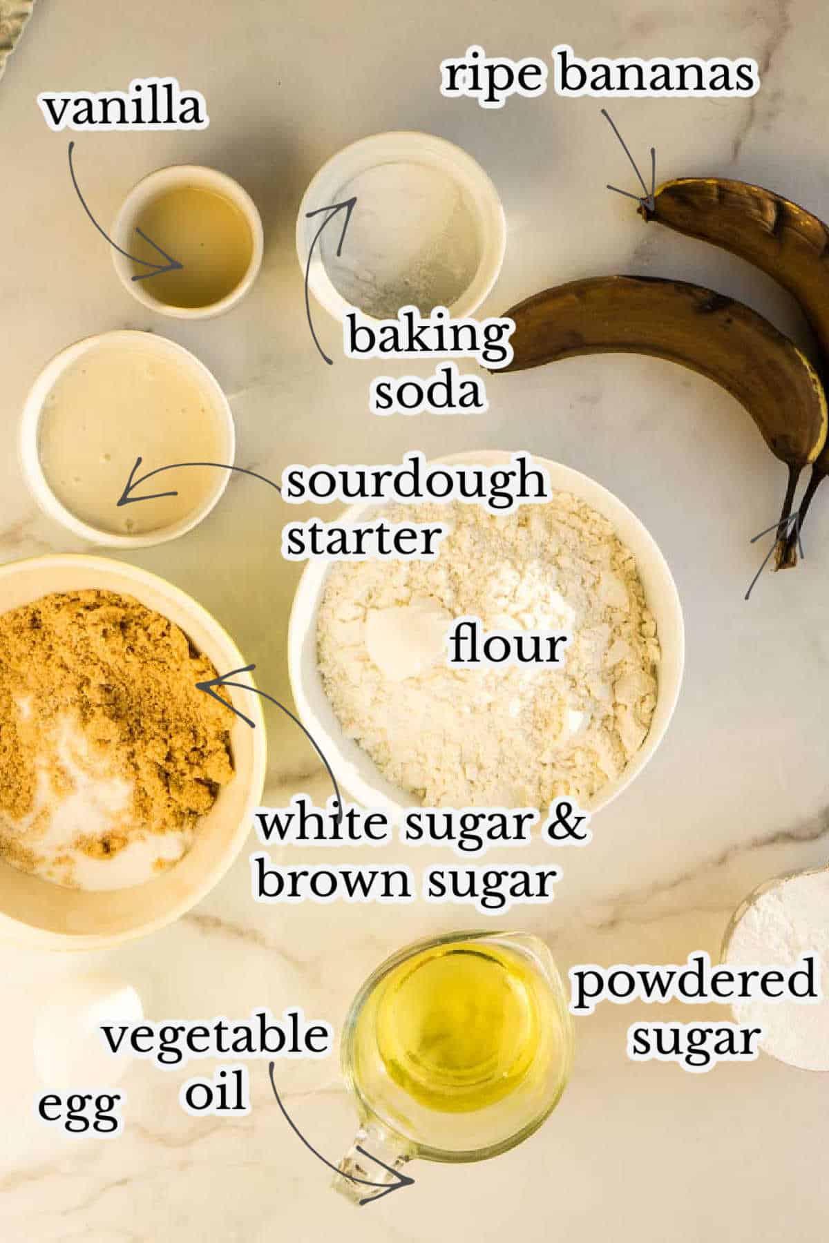 bananas, sourdough starter, baking soda, flour, sugar, powdered sugar on marble counter