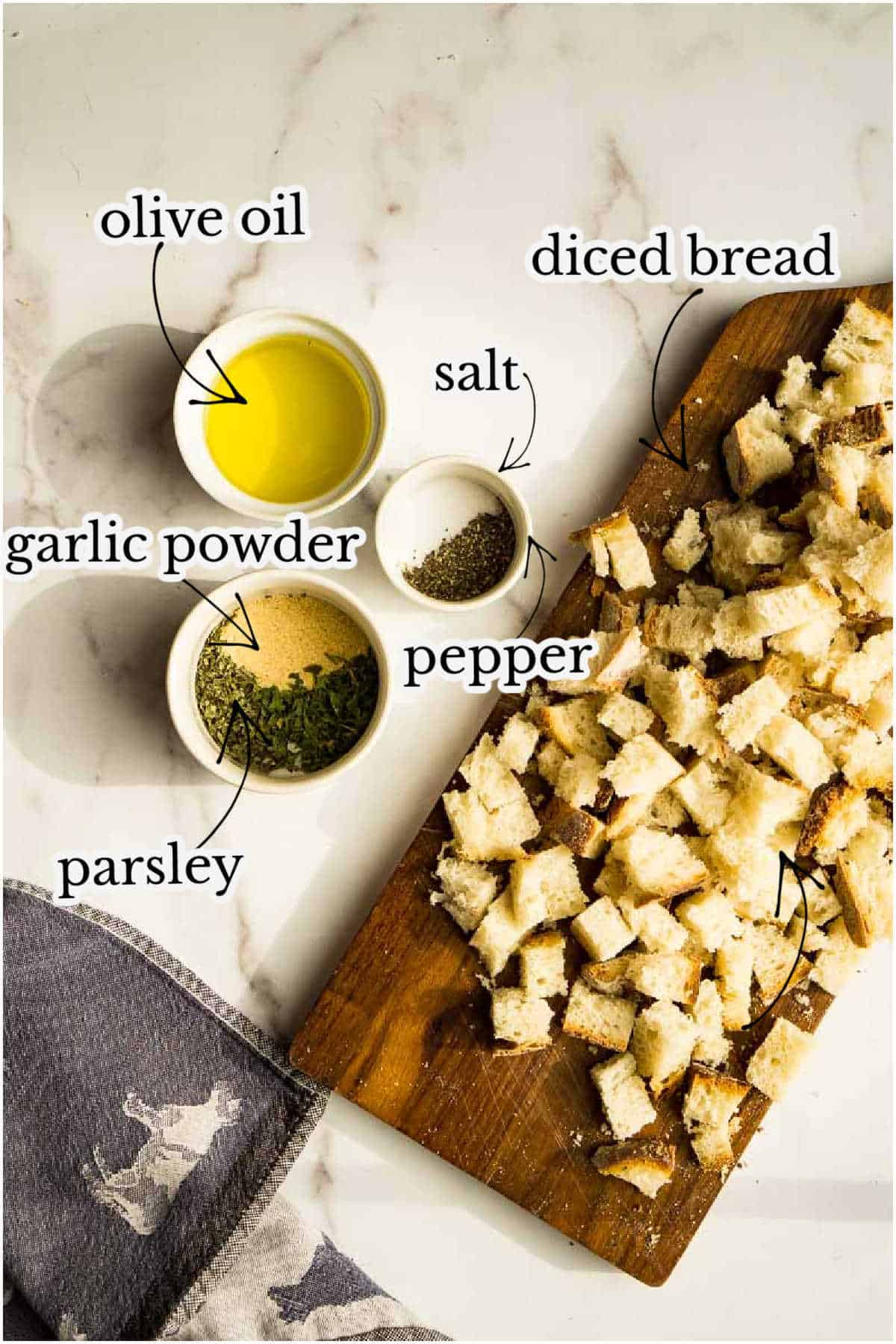 cubed bread, olive oil, salt, pepper, garlic powder, herbs on marble counter