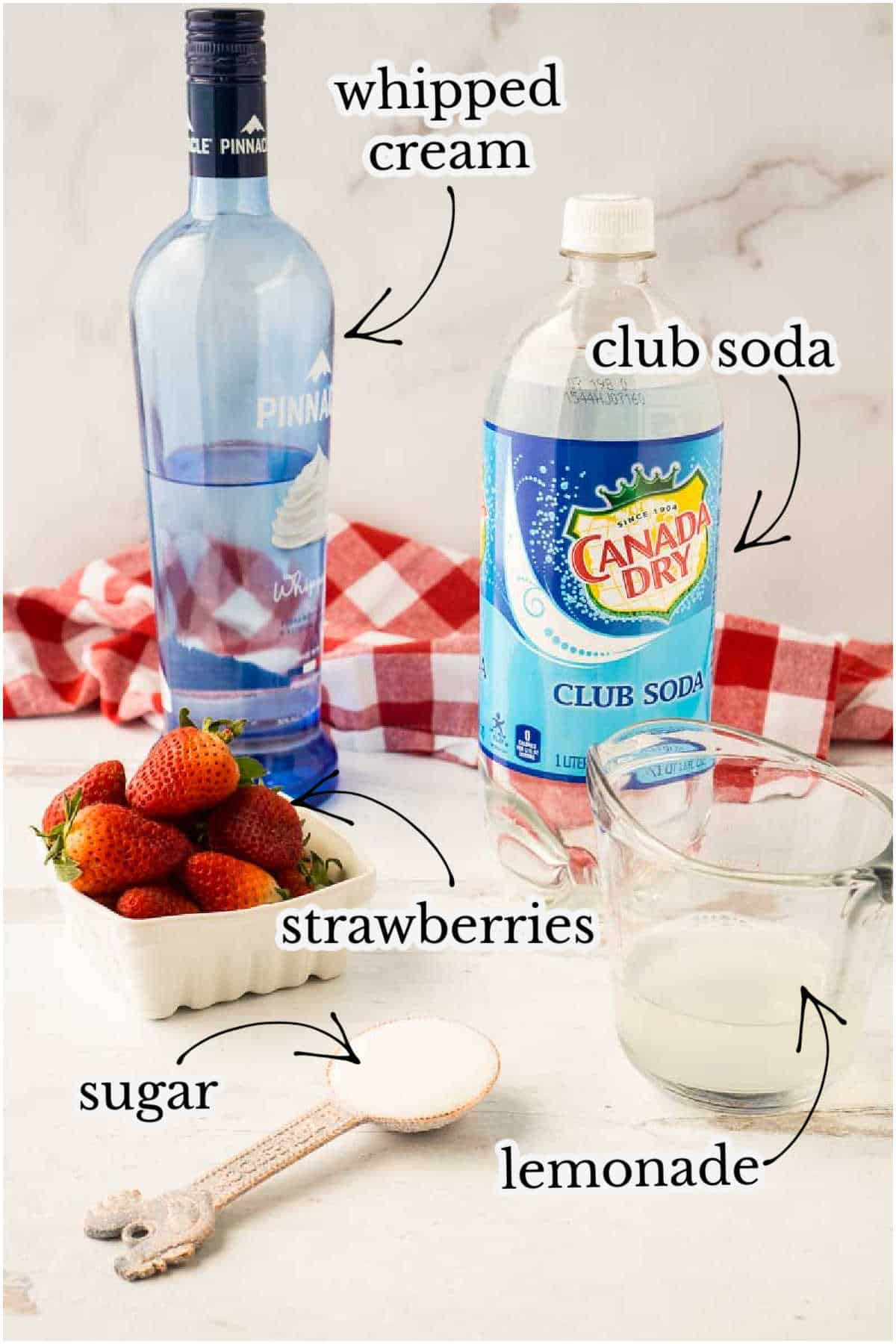 whipped cream vodka, club soda, strawberries, and lemonade on white counter