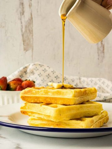 stack of sourdough waffles with syrup being poured on top