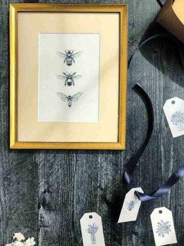 framed bee print and tag on wooden background
