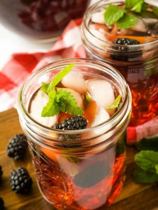 2 mason jars filled with blackberry tea on ice with fresh mint and berries