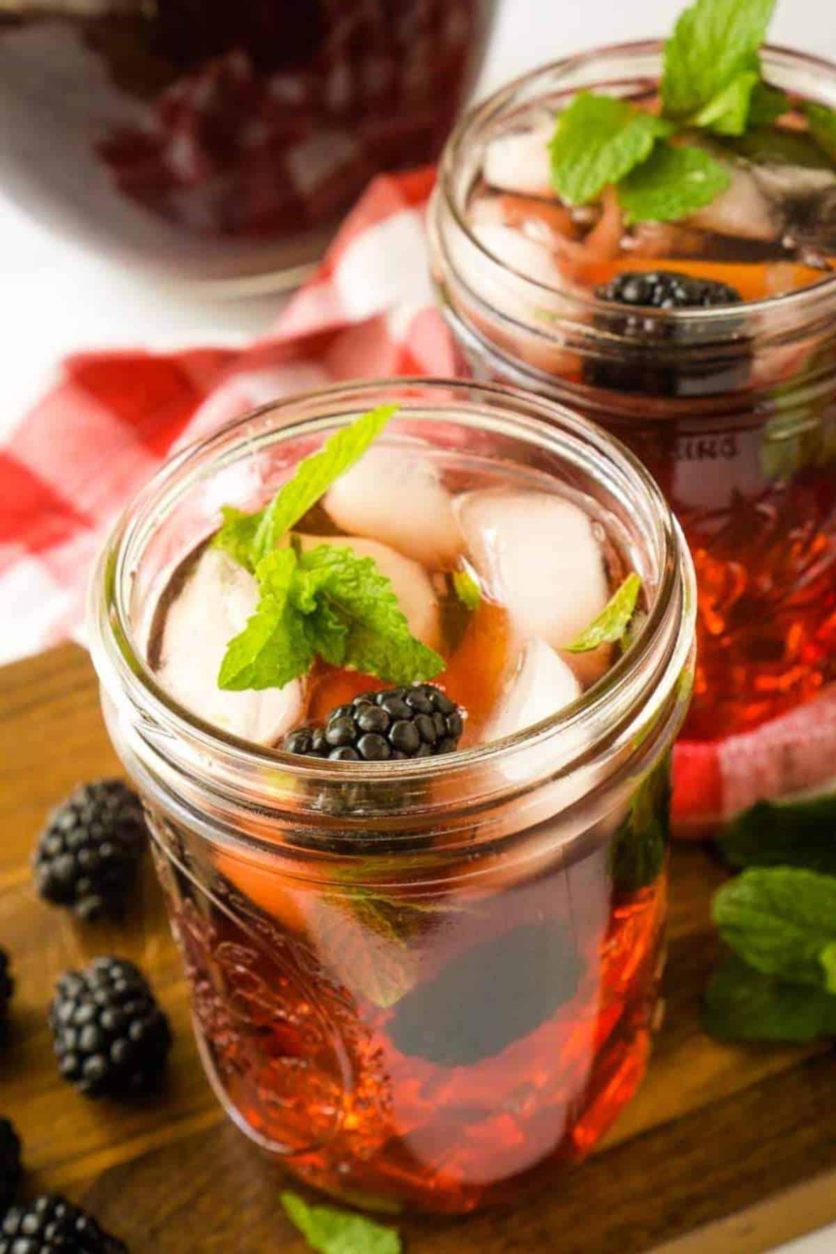 2 mason jars filled with blackberry sweet tea on ice