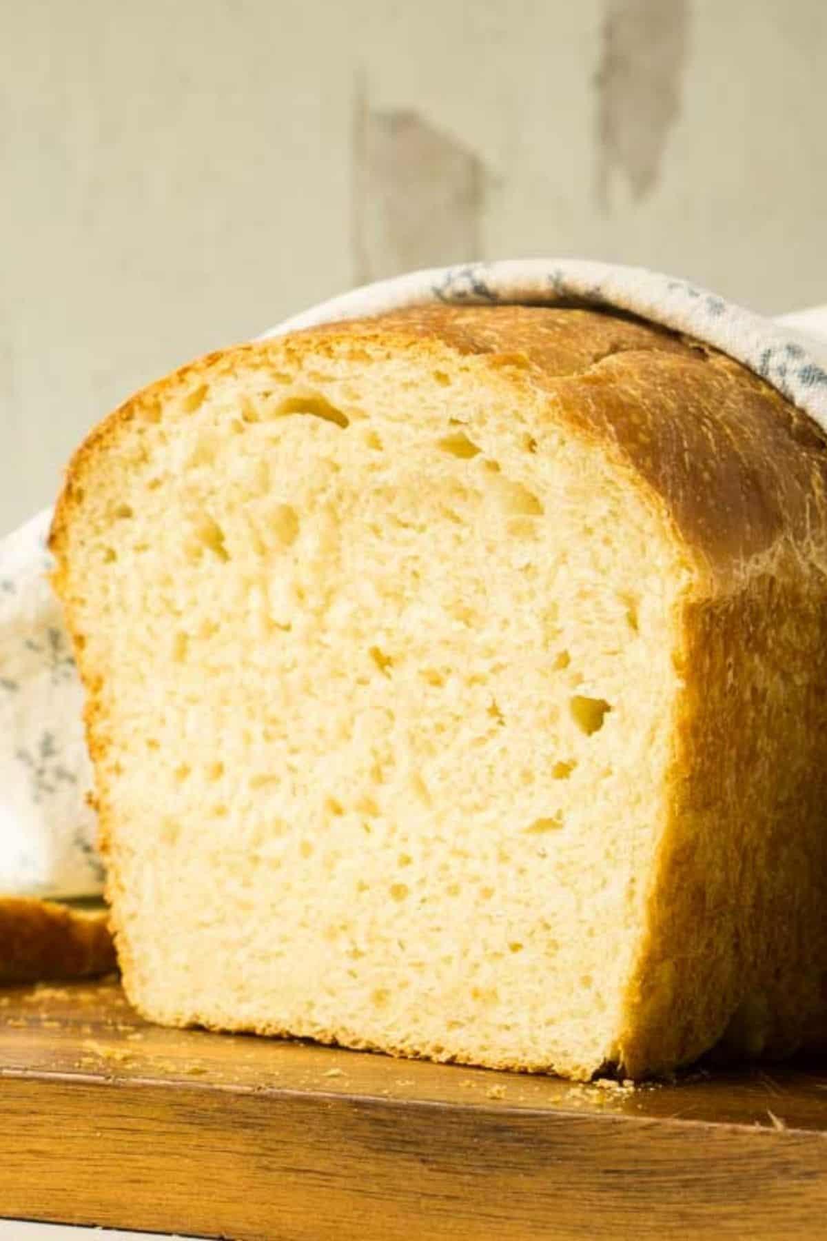 sandwich loaf of buttermilk sourdough bread, cut on wooden board