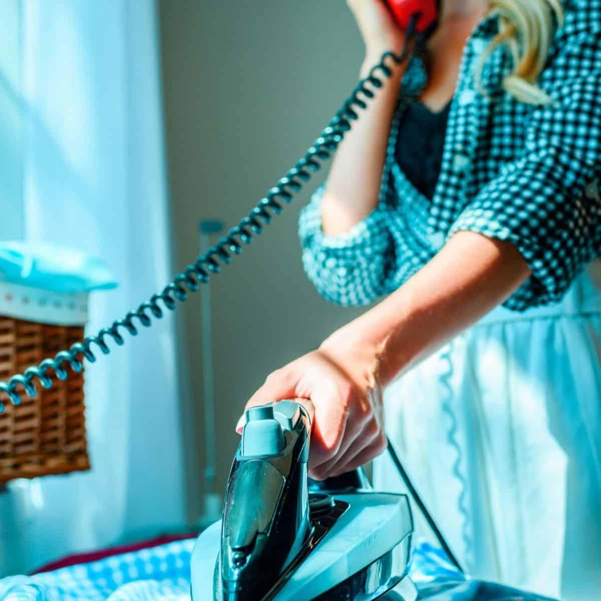 woman ironing while on landline phone