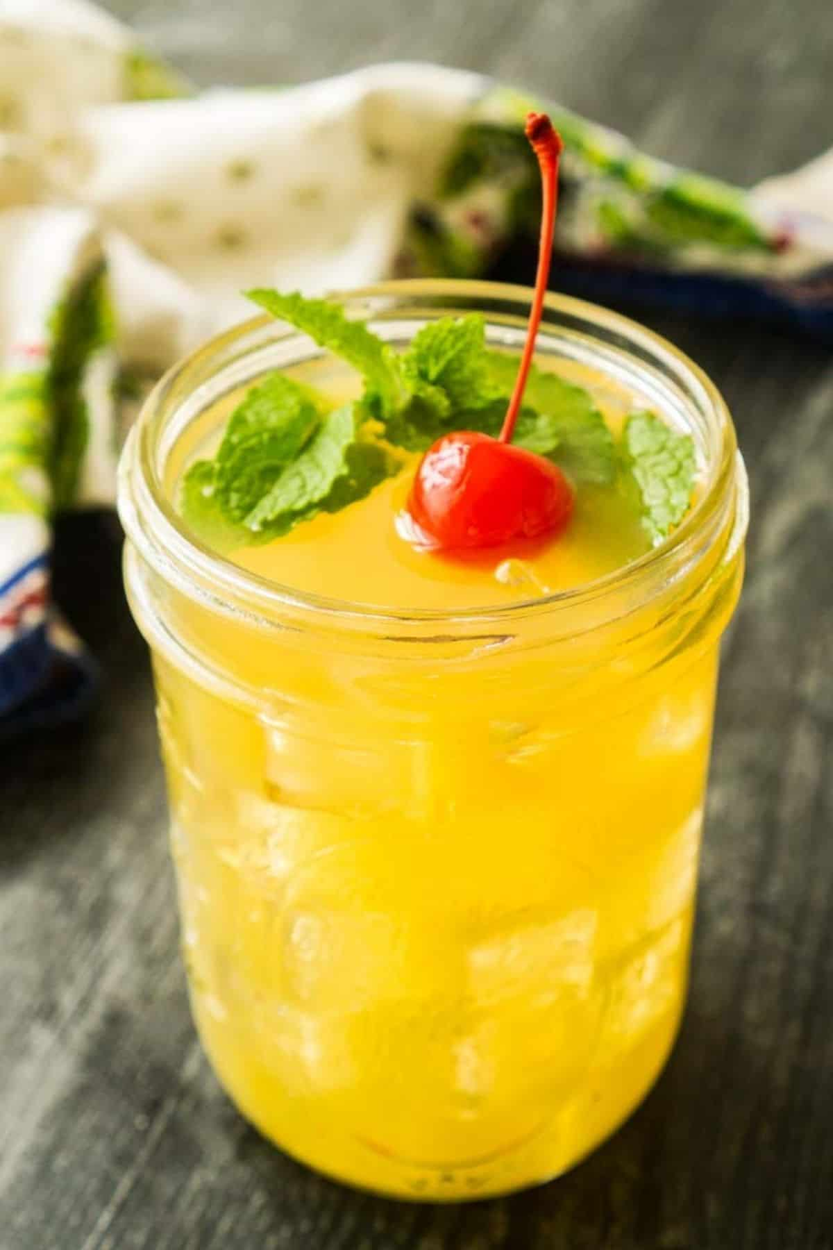 mason jar with pineapple juice cocktail with mint and cherry on top
