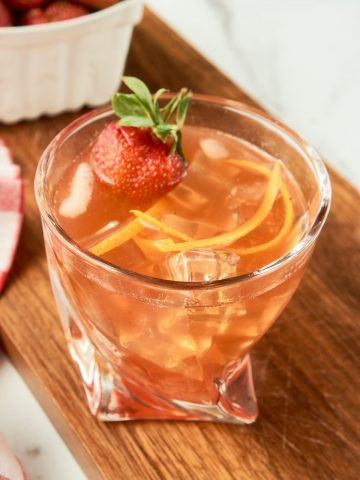 strawberry old fashioned cocktail on wooden board
