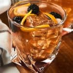 close view of old fashioned cocktail with blackberries