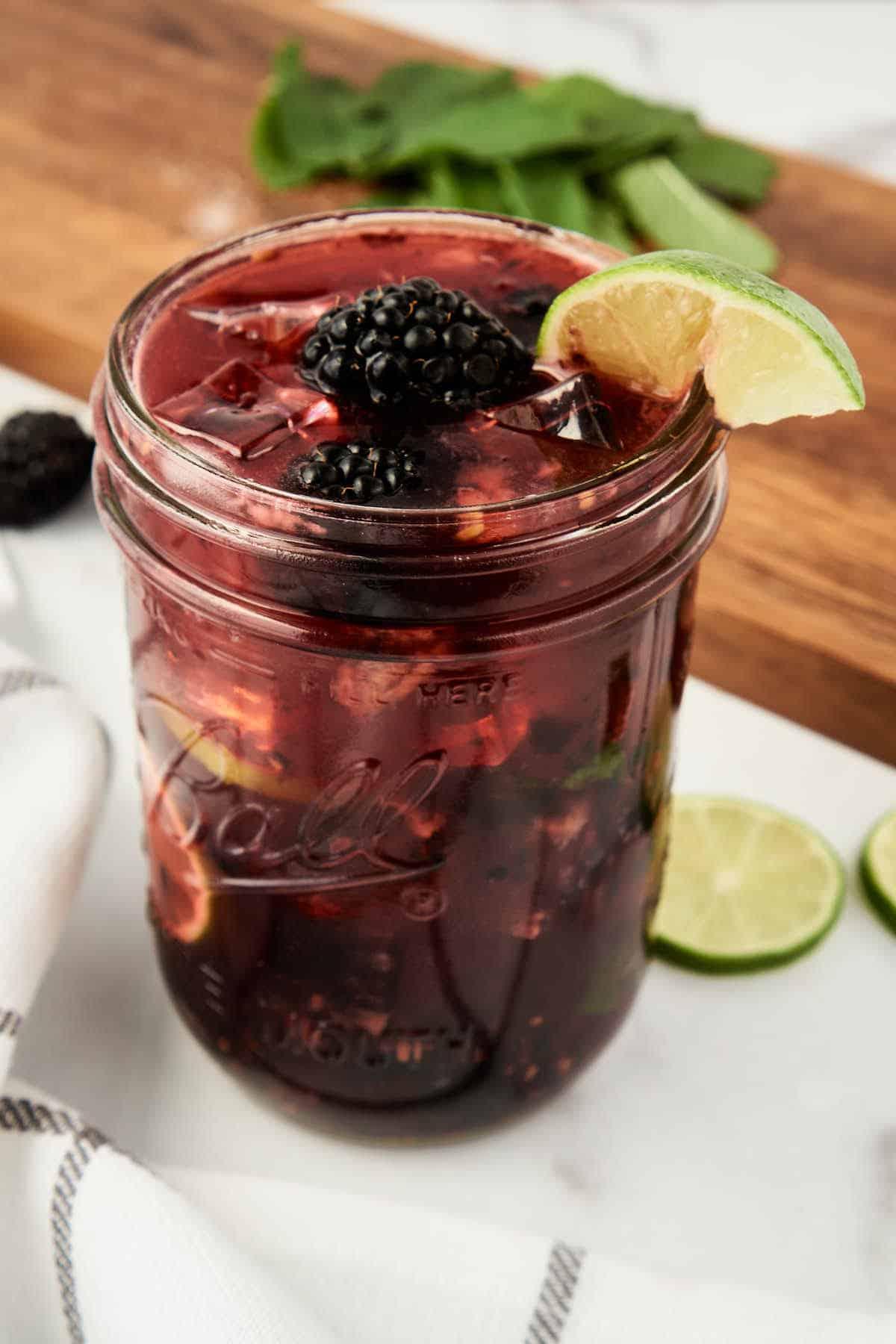 blackberry mojito in mason jar on white counter