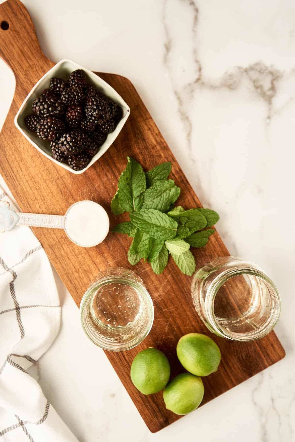 blackberries, rum, club soda, limes, sugar, and mint leaves on wooden cutting board