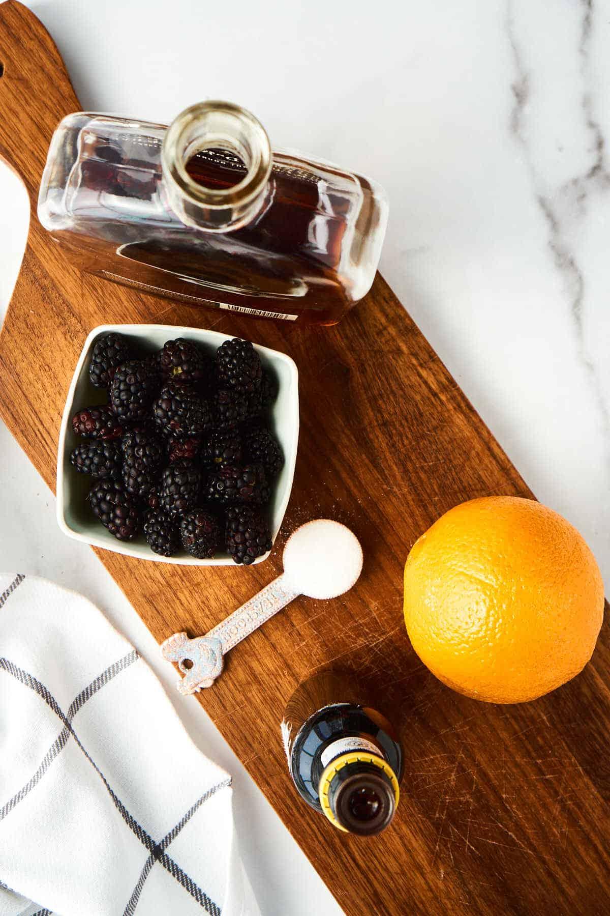 wooden board with bottle of bourbon, whole orange, basket of blueberries, sugar