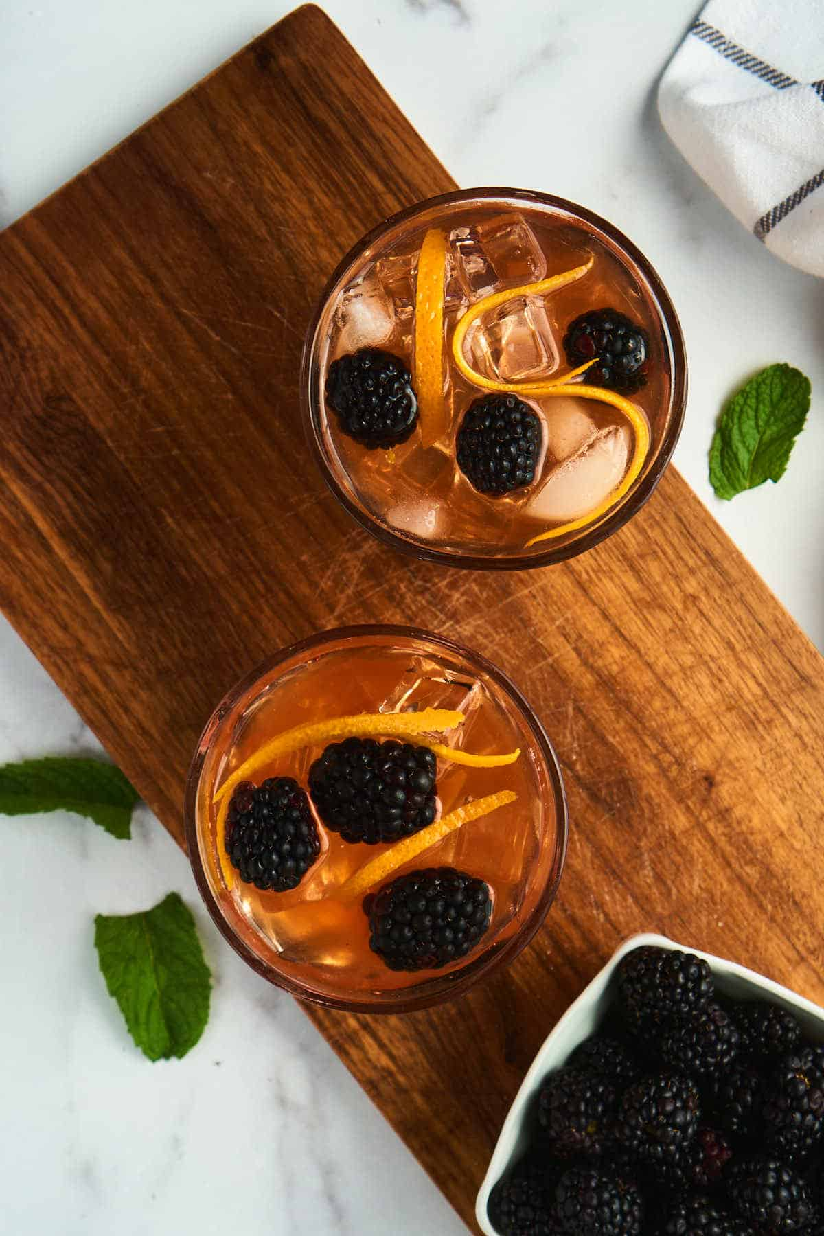 overhead view show blackberry and orange peel garnish in old fashioned glass