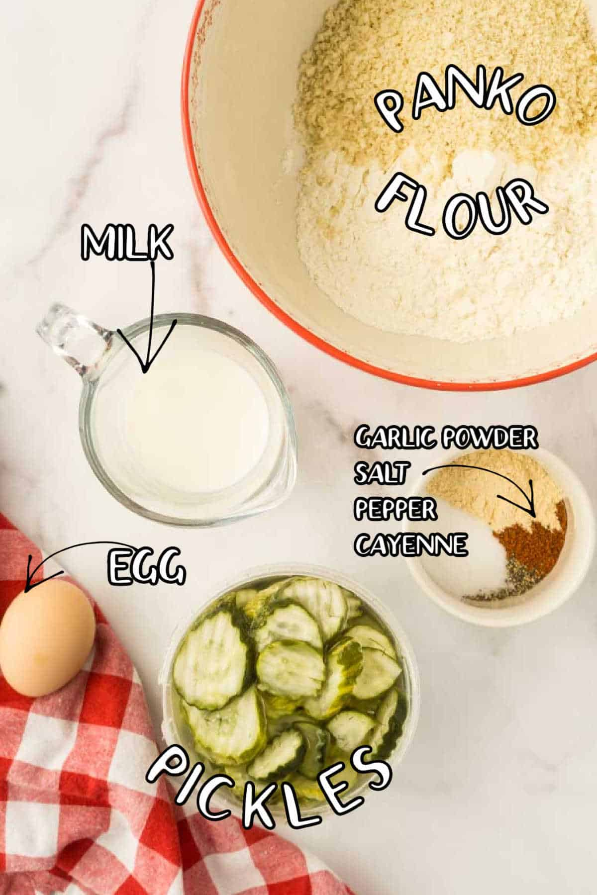 pickles, egg, milk, salt, garlic powder, pepper, flour, and bread crumbs in bowls on counter