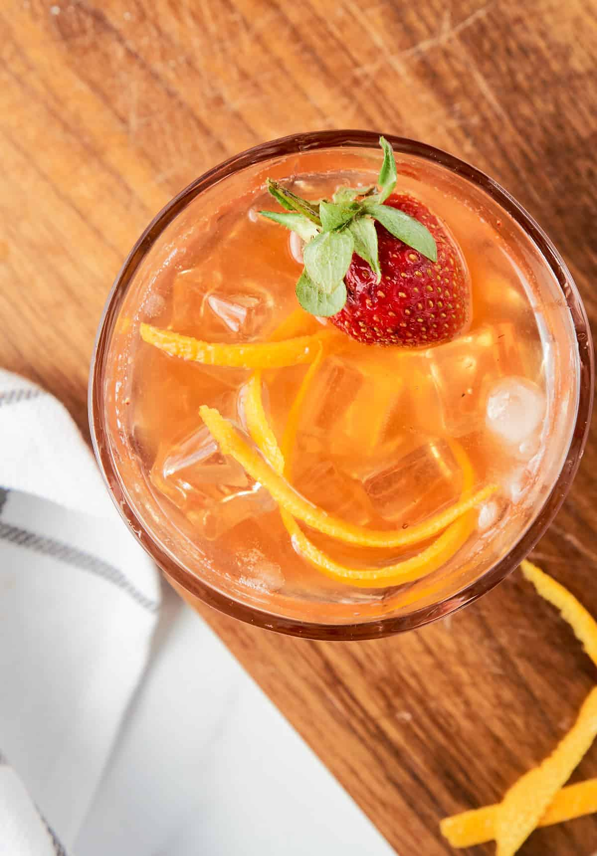 overhead view of old fashioned cocktail with orange peel and strawberry on top
