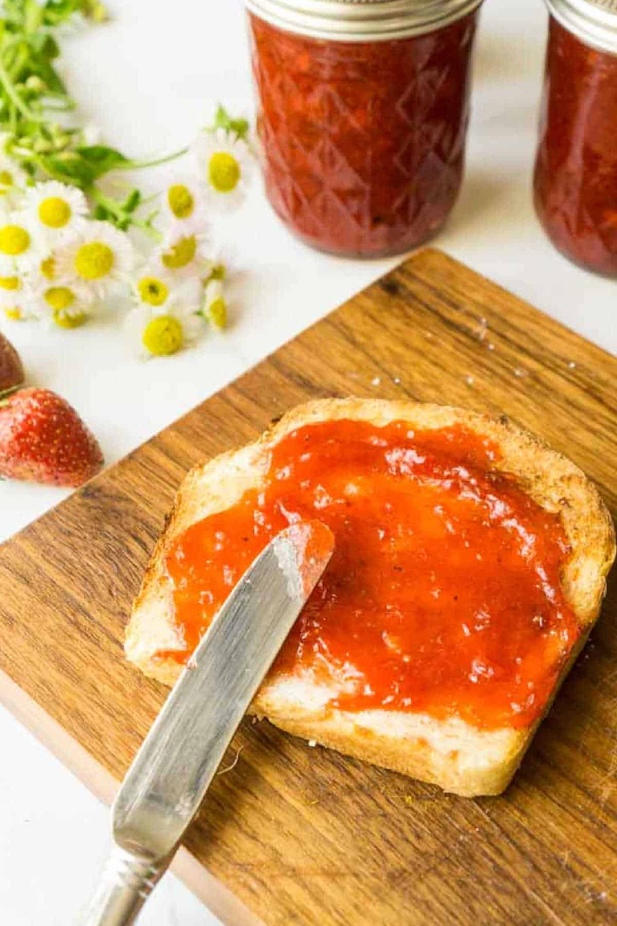 cutting board with slice of toast spreading on strawberry jam