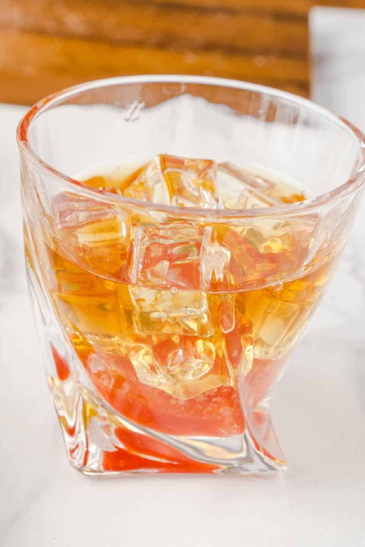 rocks glass showing strawberry syrup on bottom and bourbon layer on top