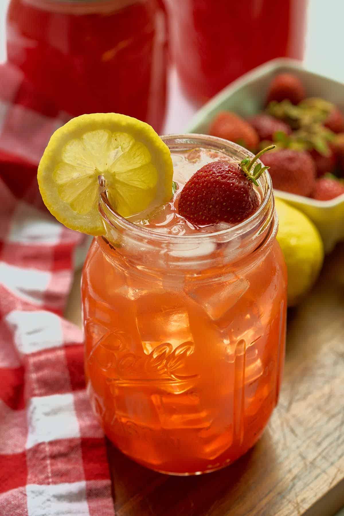 mason jar full of strawberry lemonade on ice