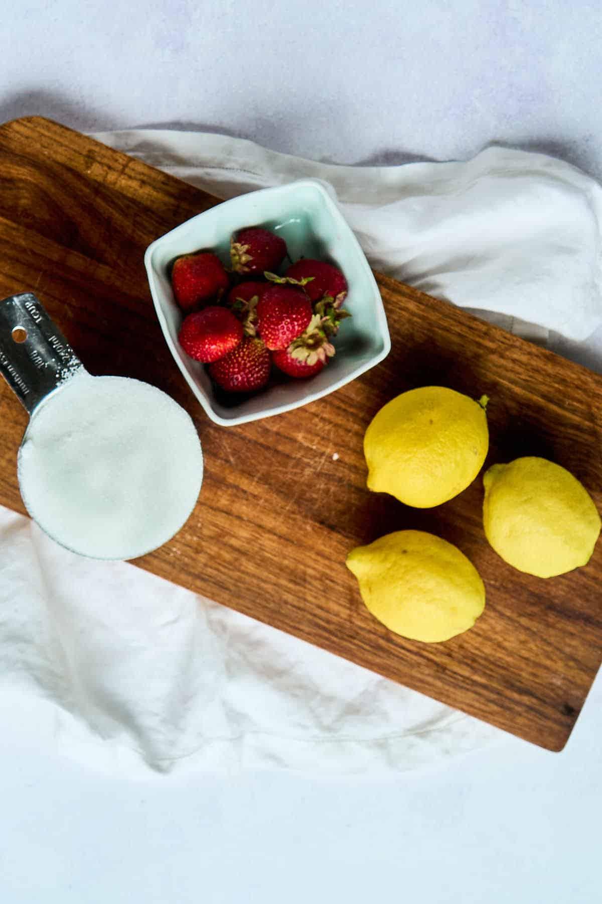 lemons, strawberries, and sugar on cutting board