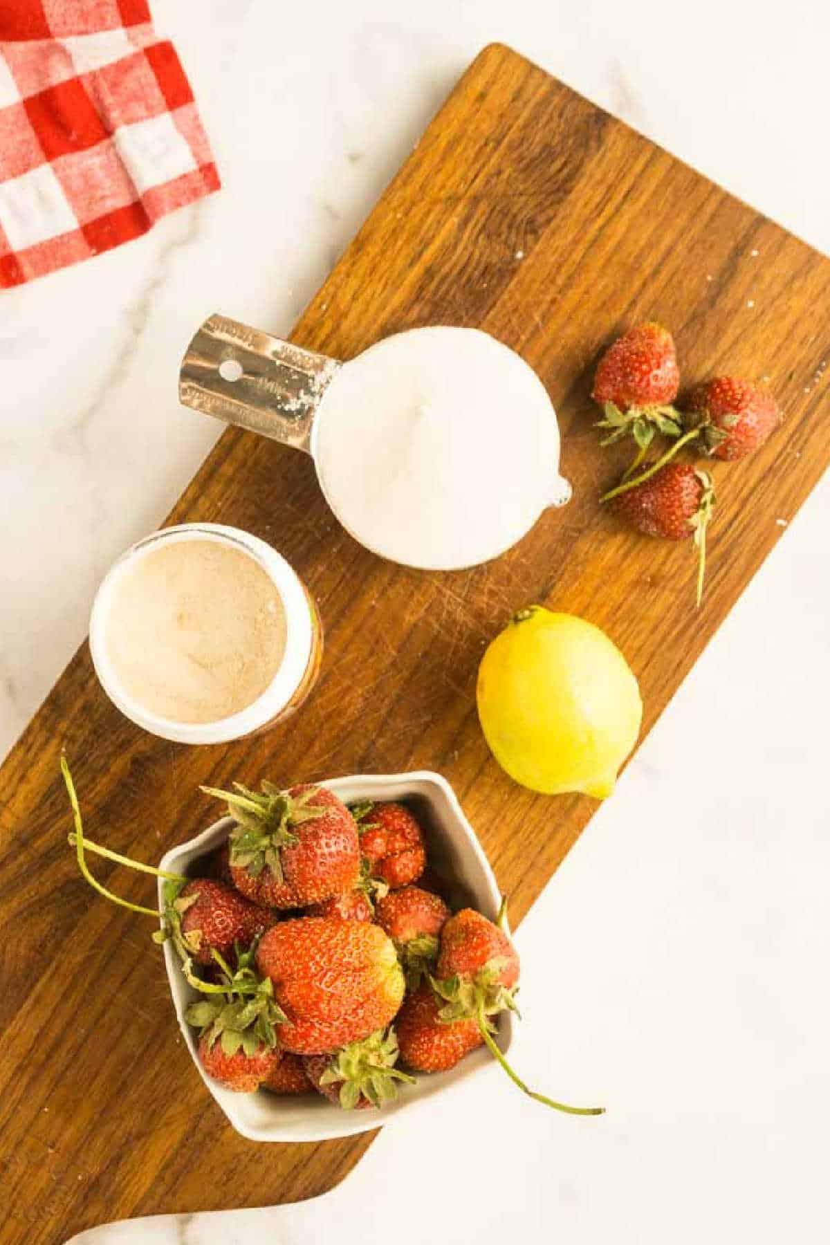 cutting board with sugar, pectin, fresh strawberries, and lemon