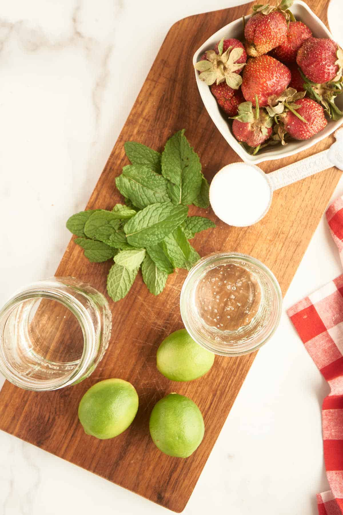 wooden board with fresh mint, strawberries, limes, club soda, and white rum
