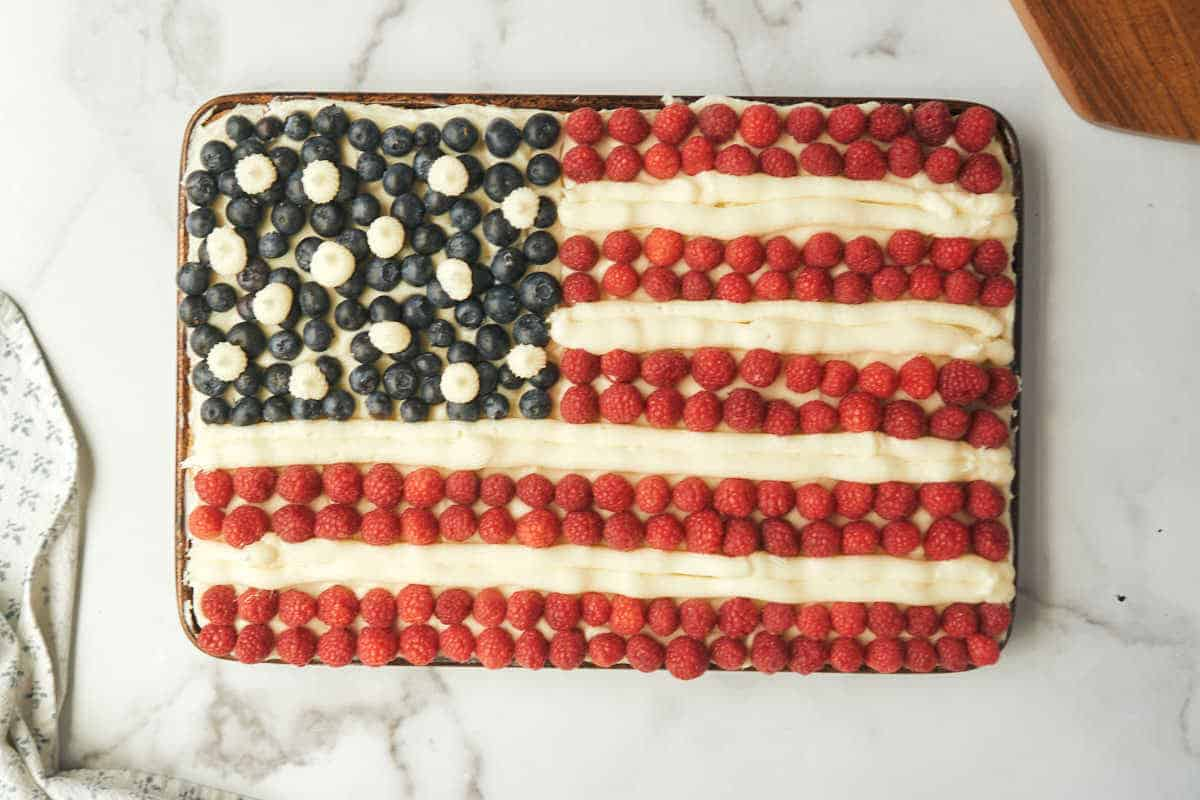 finished flag sheet cake with raspberries for red strips, blueberries for stars and piped cream cheese frosting
