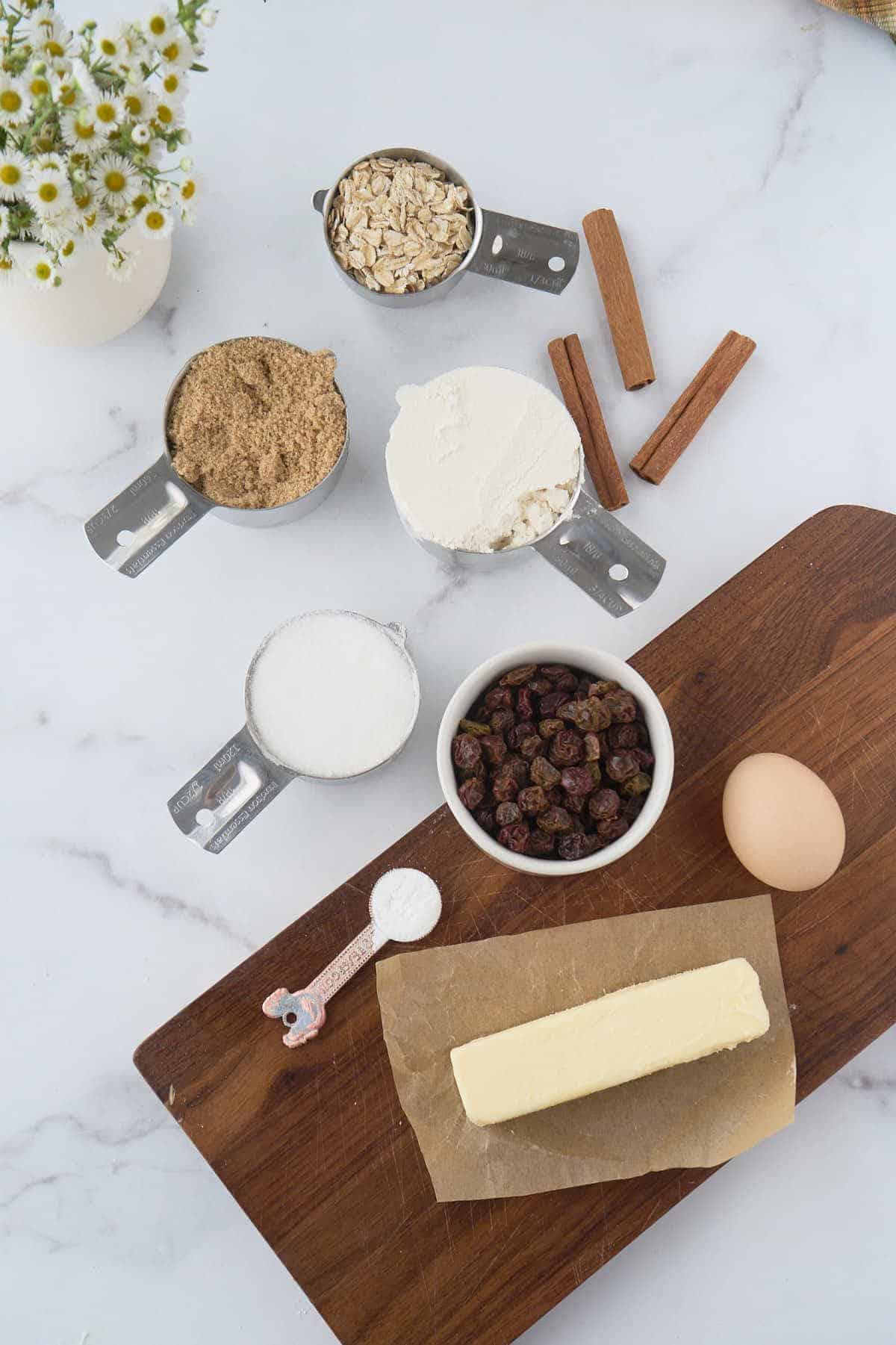 butter, sugar, oats, flour, raisins, and cinnamon sticks on marble counter