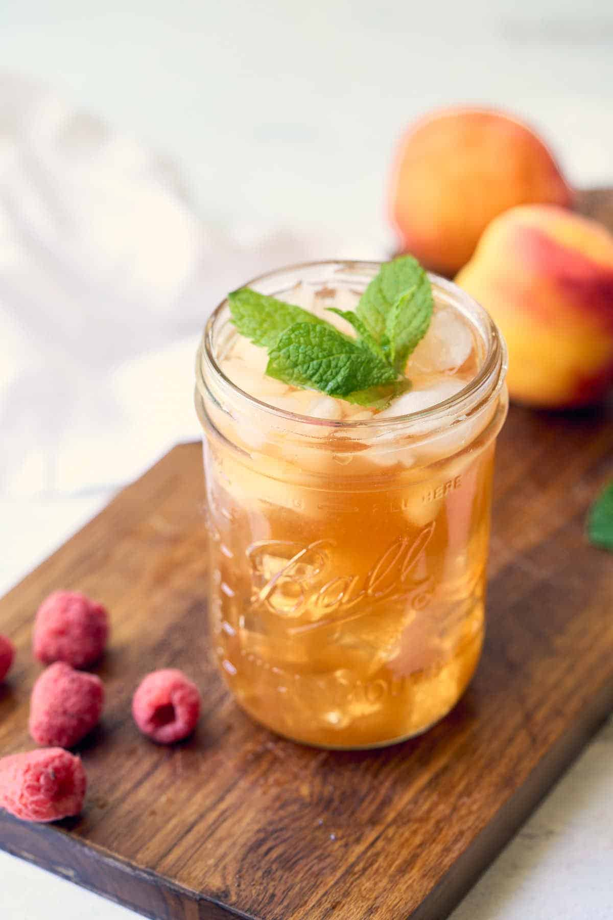 pint size mason jar with iced tea: fresh peaches and raspberries in background