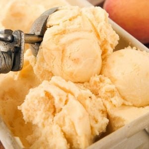 three scoops peach ice cream being scooped with vintage scoop