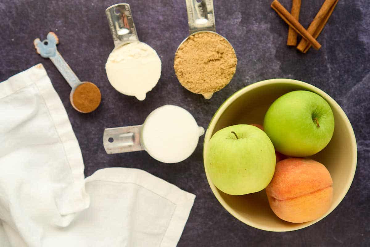 sugar, brown sugar, apples, peaches. and cinnamon in bowls