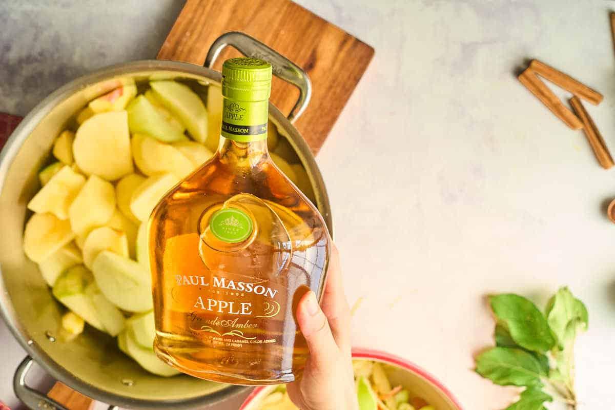 apple brandy bottle in frony of bowl of apples