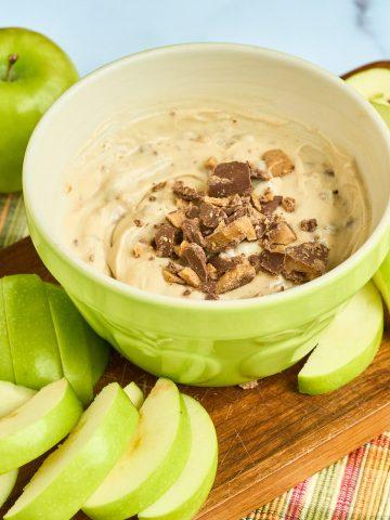green apple slices surrounding bowl of cream cheese fruit dip