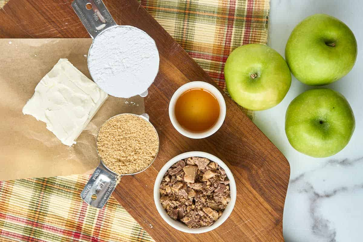 counter with cream cheese, powdered sugar, brown sugar, apples, and crushed heath bars