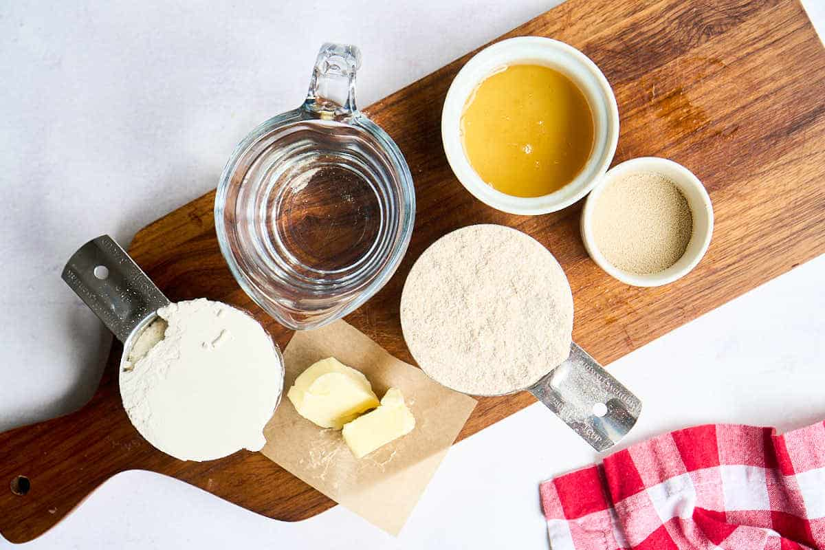 water, honey, wheat flour, white flour, and butter on wooden board