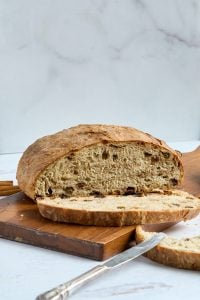cutting board with loaf of raisin bread and butter