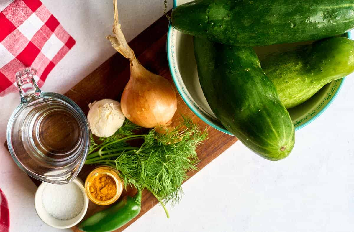 cucumbers, pickles, dill, vinegar, salt, and turmeric on wooden board