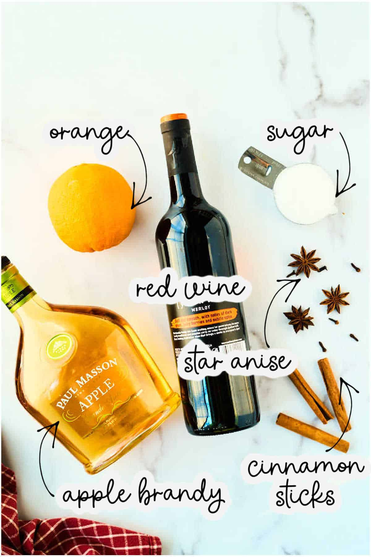 bottle of red wine, cinnamon sticks, sugar, star anise, and apple brandy on marble counter