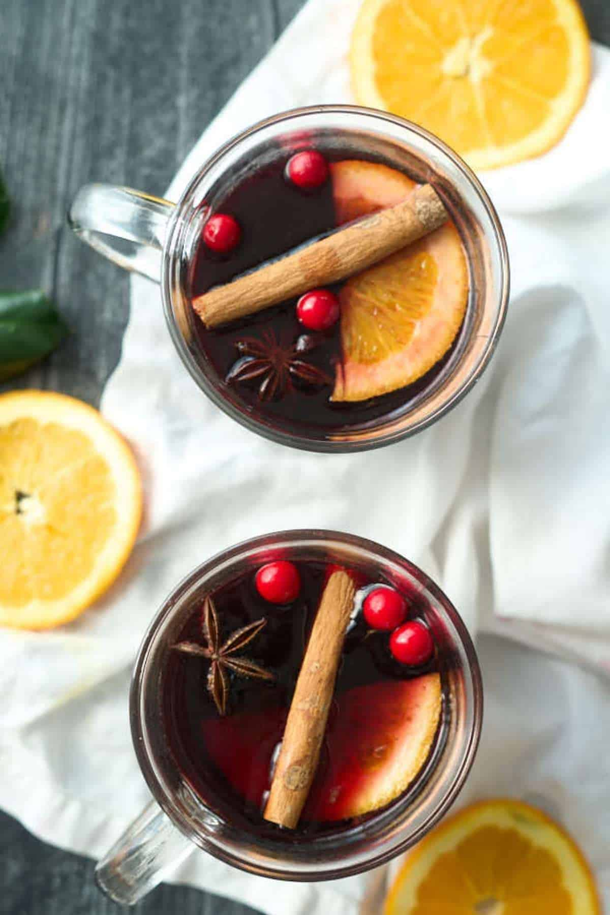 2 cups mulled red wine in clear mug with cinnamon sticks