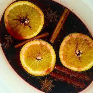 slow cooker filled with wine topped with orange slices and cinnamon sticks