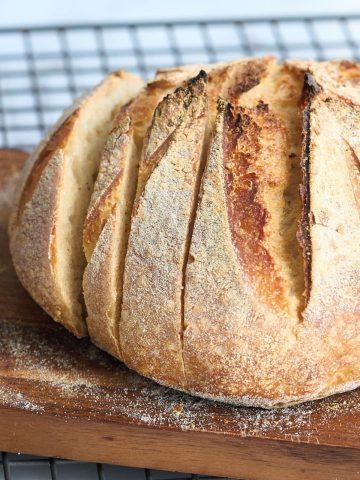 loaf of sourdough bread on cooling rack being sliced