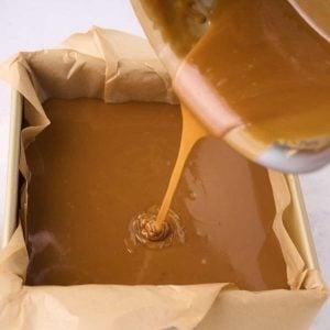 saucepan pouring caramel into dish