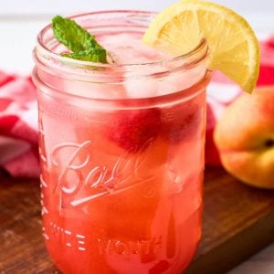 mason jar with pink lemonade made from peaches and raspberries