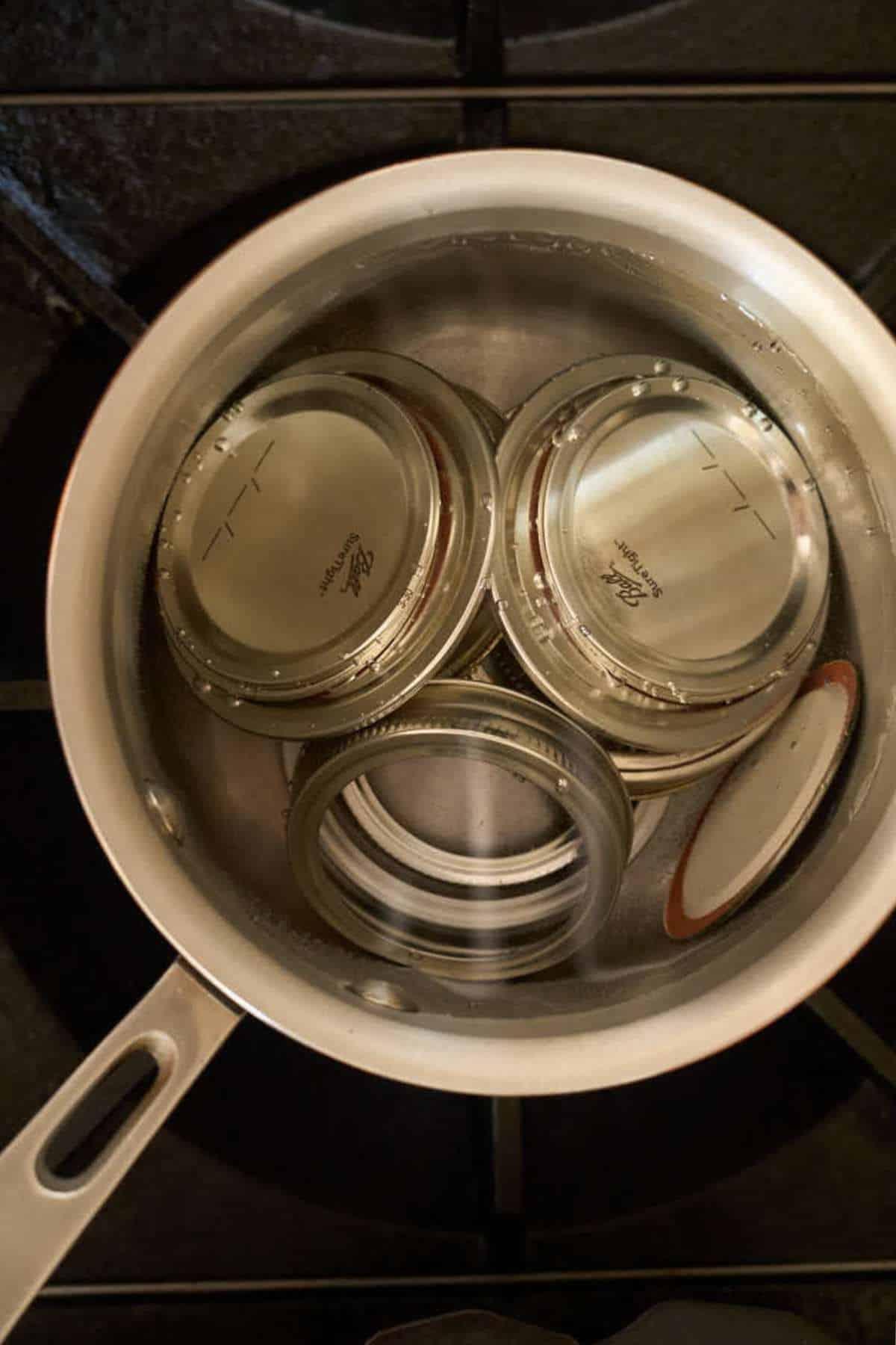 jar lids and rings in simmering water