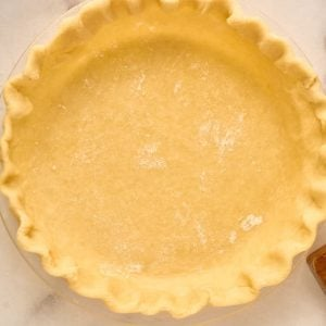 crimped pastry pie crust in glass plate