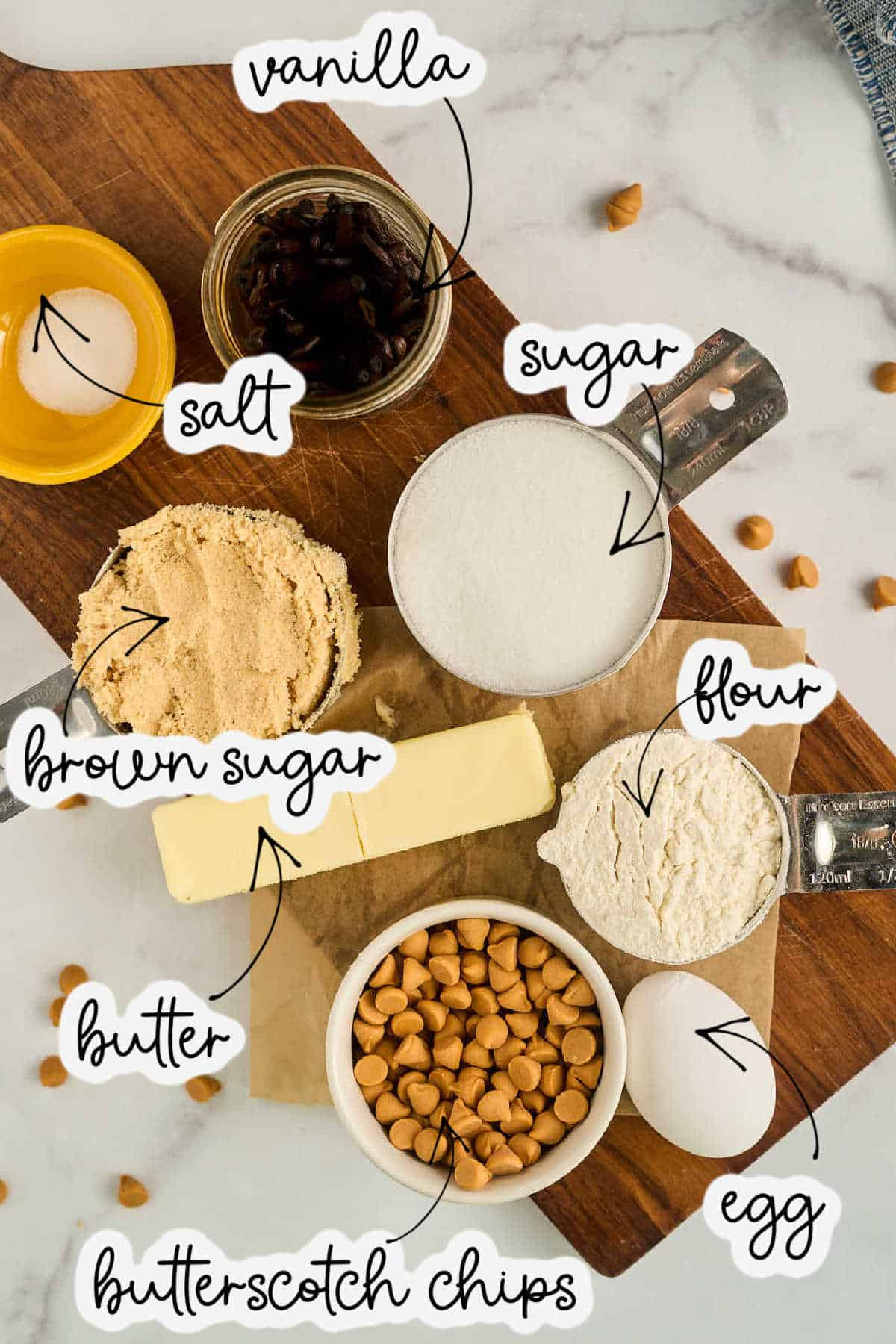 sugar, flour, brown sugar, sugar, and butterscotch chips on marble counter